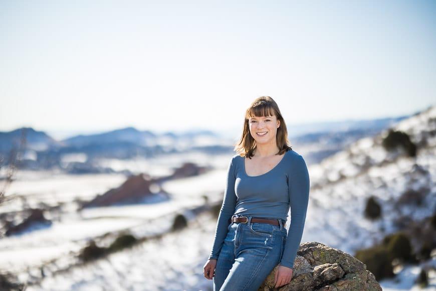 Woman sitting on rock in snow