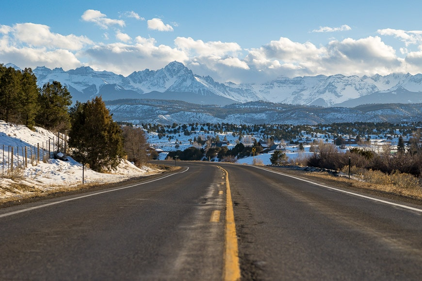 Road snaking off into snow-capped mountains
