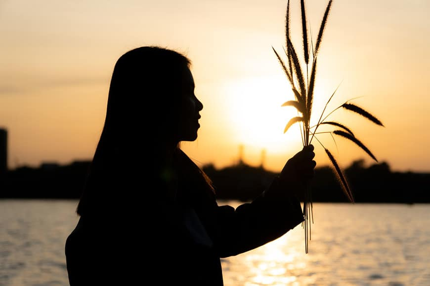 Girl holding bunch of grass silhouetted against the sun