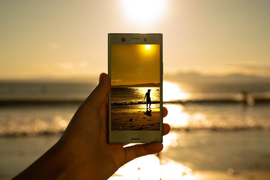 Image of a person on the beach captured on smartphone