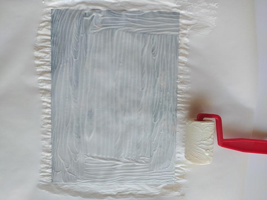 Applying modge podge atop wax paper