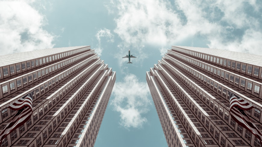 Aeroplane flying above symmetrical buildings