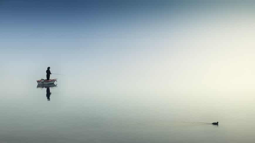 Fisherman in a small boat against empty shape of water and sky